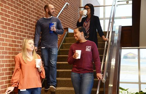 Four ATFCU employees descending staircase