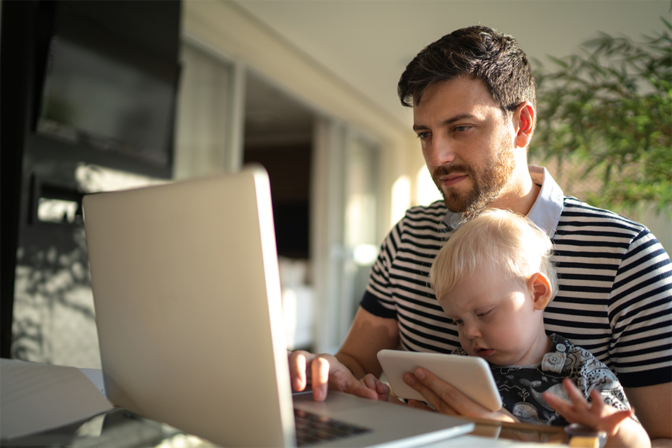 Male with child in his lap using a laptop computer