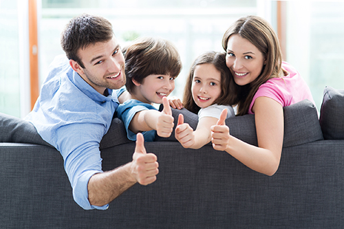 family on sofa with thumbs up