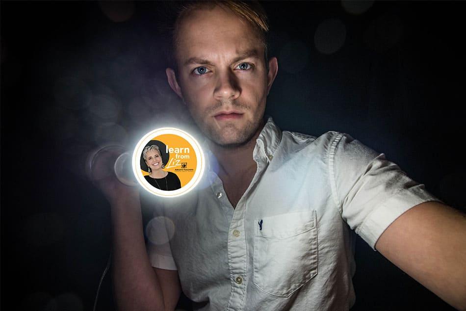 man holding a flashlight in the dark
