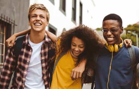 Three teens walking down street