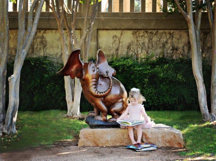 Little girl reading in sculpture park