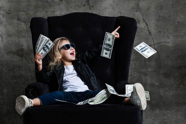 Young girl in velvet chair with play money