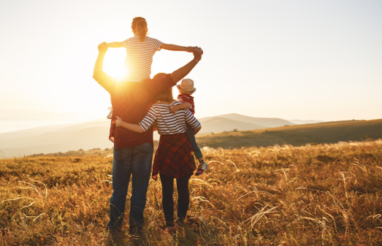 Family in field watching sunrise