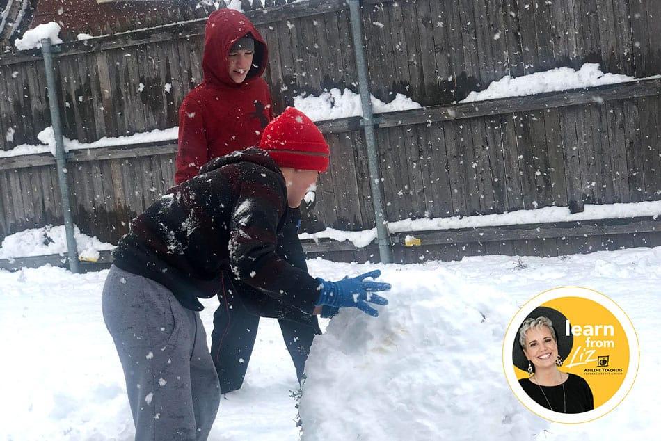 two boys making a big snowball