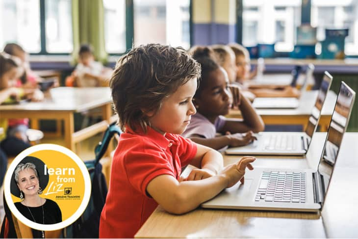 children in a classroom on laptops