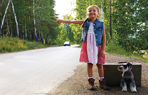 Young girl playfully hitchhiking