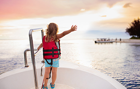 child standing at front of boat