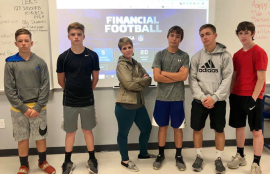 Group of young teens playing Financial Football with teacher
