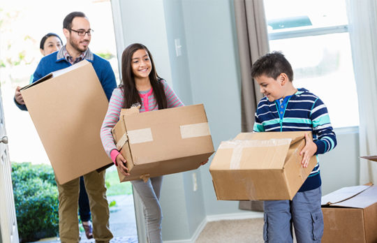 family moving boxes to new home