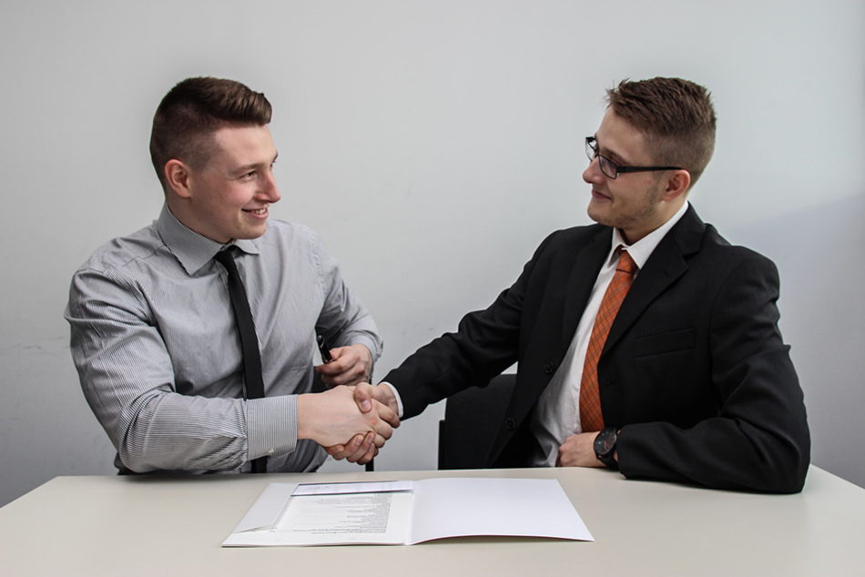 Two young men shaking hands on a deal