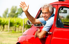 man in red vintage car waving