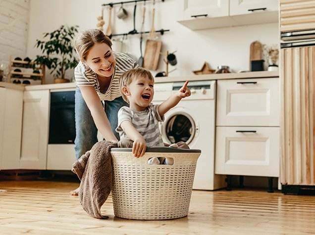mother pushing son in laundry basket