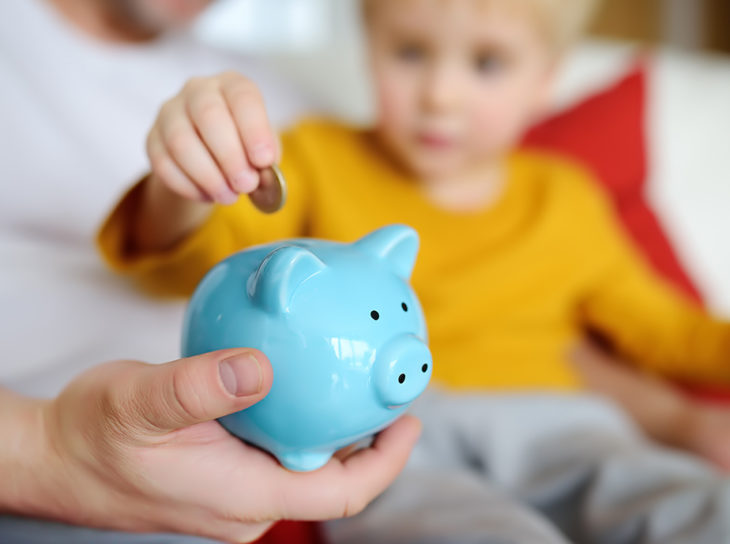Child depositing coins in piggy bank