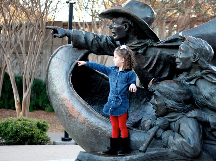 pointing girl with Santa Calls statue